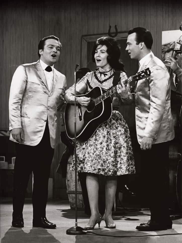 Lynn performing with Doyle (left) and Teddy Wilburn, the Wilburn Brothers, 1960s. Photo by Sid O'Berry