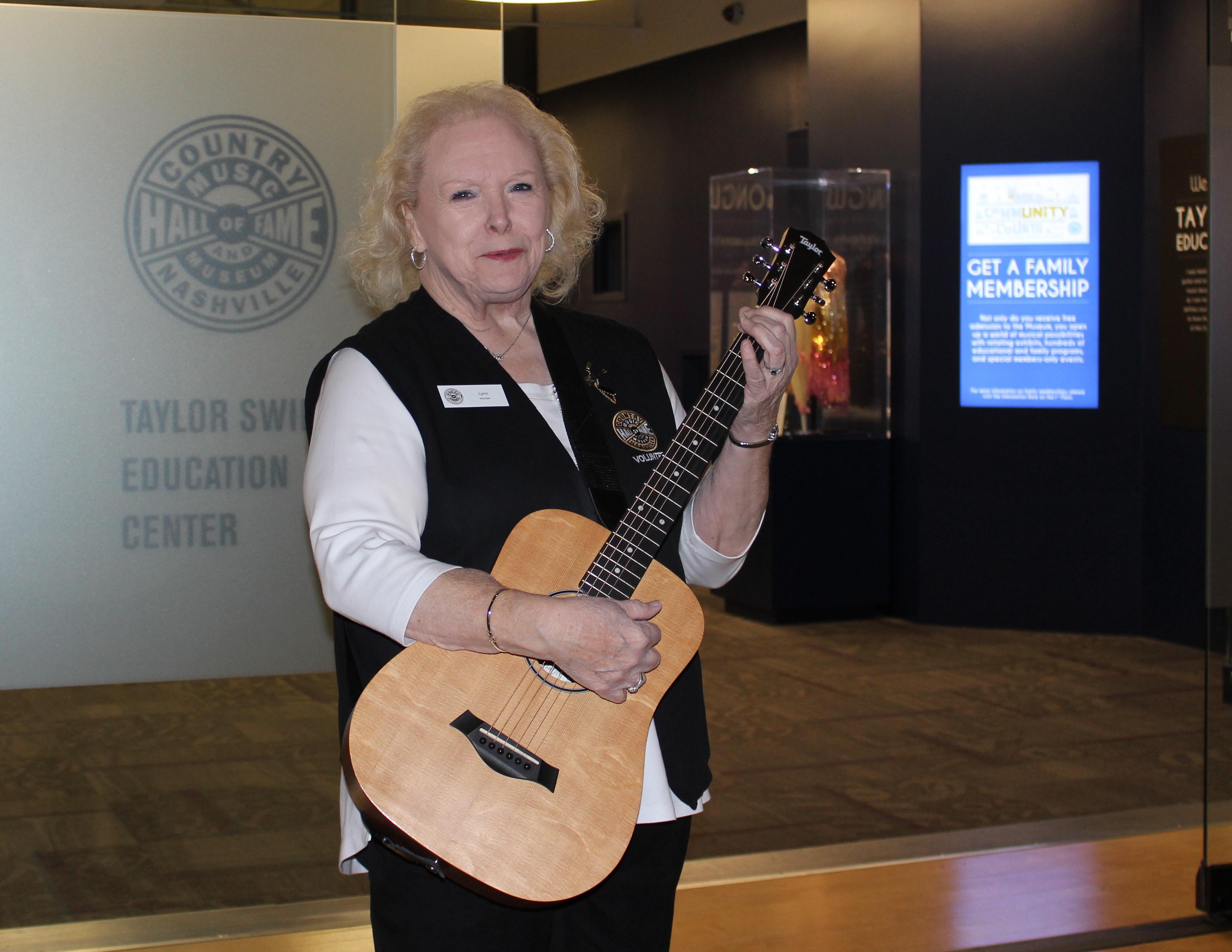 Volunteer Lynn Nolan holding guitar